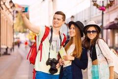 Muchachas e individuo que toman selfies con el teléfono móvil Imagen de archivo