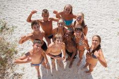 Muchachas e individuos en la arena el vacaciones de verano Foto de archivo