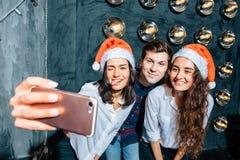 Muchachas e individuos en los sombreros de Papá Noel que hacen el selfie en el partido La Navidad, concepto del Año Nuevo Fotografía de archivo