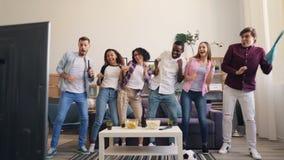 Muchachas e individuos que bailan y que ríen después de la victoria en juego de los deportes en la TV en casa metrajes