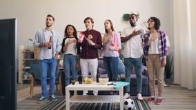 Muchachas e individuos que cantan las banderas que agitan del himno canadiense que miran fútbol en la TV almacen de metraje de vídeo