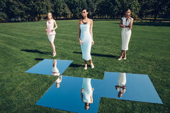 Muchachas elegantes hermosas que presentan en campo de golf con la hierba verde y los espejos imagenes de archivo