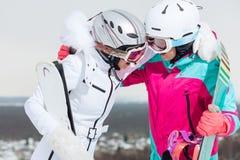 Muchachas elegantes que tienen humor positivo durante la reclinación en la estación de esquí fotos de archivo