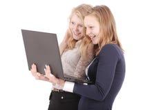 Muchachas emocionadas que miran los vídeos en el ordenador portátil Fotos de archivo libres de regalías