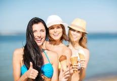 Muchachas en bikini con helado en la playa Fotografía de archivo