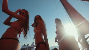 Muchachas en bikini y con las buenas figuras que se divierten