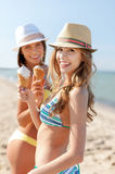 Muchachas en bikinis con helado en la playa Imagen de archivo libre de regalías
