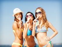 Muchachas en bikinis con helado en la playa Foto de archivo