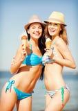 Muchachas en bikinis con helado en la playa Imágenes de archivo libres de regalías
