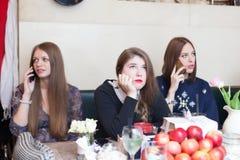 Muchachas en cafetería que hablan en el teléfono celular Imagen de archivo