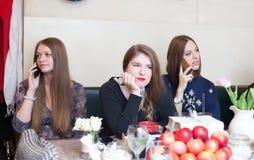 Muchachas en cafetería que hablan en el teléfono celular Imagen de archivo libre de regalías