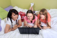 Muchachas en cama usando la computadora portátil Fotos de archivo libres de regalías