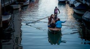 Muchachas en el barco en el canal veneciano