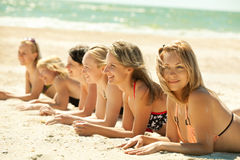 Muchachas en el bikiní que miente en la playa Imagen de archivo