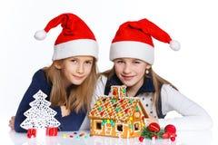 Muchachas en el sombrero de Papá Noel con la casa de pan de jengibre Fotos de archivo