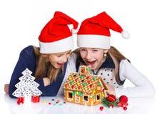 Muchachas en el sombrero de Papá Noel con la casa de pan de jengibre Fotografía de archivo