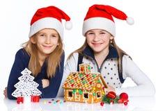 Muchachas en el sombrero de Papá Noel con la casa de pan de jengibre Foto de archivo