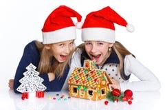 Muchachas en el sombrero de Papá Noel con la casa de pan de jengibre Imágenes de archivo libres de regalías