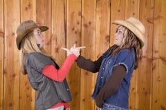 Muchachas en granero que señalan caras divertidas Imagen de archivo libre de regalías