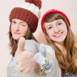 Muchachas en guantes hechos punto y sombrero que muestra los pulgares para arriba Imagen de archivo libre de regalías
