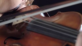 Muchachas en juego los violines en una composición en un cuarto Fondo negro Cierre para arriba almacen de video