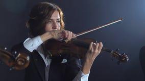 Muchachas en juego los violines en una composición en un cuarto Fondo negro del humo almacen de video