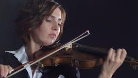 Muchachas en juego los violines en una composición en un cuarto Fondo negro del humo almacen de metraje de vídeo