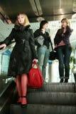 Muchachas en la escalera móvil en el aeropuerto fotografía de archivo libre de regalías