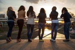 muchachas en la puesta del sol en el parque de la ciudad Fotos de archivo