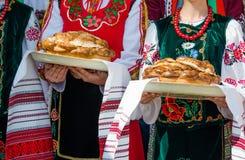 Muchachas en la ropa búlgara étnica que sostiene el pan hermoso tradicional imagen de archivo libre de regalías