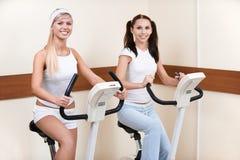 Muchachas en las bicis de ejercicio Fotos de archivo libres de regalías
