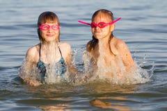 Muchachas en las gafas de la natación que bucean y que se ríen del mar en un wa Fotos de archivo libres de regalías