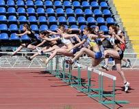 Muchachas en los 100 contadores de la carrera de vallas Fotografía de archivo
