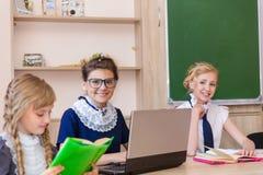 Muchachas en los escritorios de la escuela Fotos de archivo