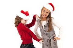 Muchachas en los sombreros de santa que se divierten que juega alrededor Imagen de archivo libre de regalías