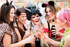 Muchachas en los vidrios que tintinean del desfile de carnaval con champán imagenes de archivo