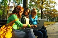 Muchachas en parque con la computadora portátil Fotos de archivo