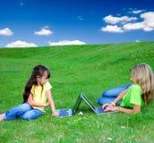 Muchachas en prado con las computadoras portátiles foto de archivo