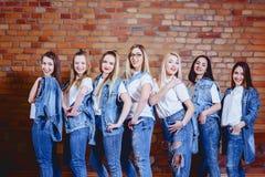 muchachas en vaqueros en el fondo de la pared de ladrillo imagenes de archivo