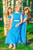 Muchachas en vestidos azules con las guirnaldas en las cabezas Imagenes de archivo