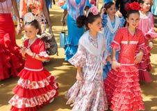 Muchachas españolas en vestido tradicional que caminan junto a Casitas en la Sevilla favorablemente Fotos de archivo