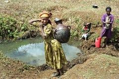 Muchachas etíopes que traen el agua en pozo de agua natural Imagen de archivo