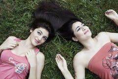 Muchachas felices brillantes en hierba Fotos de archivo libres de regalías