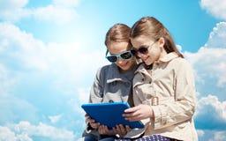 Muchachas felices con el ordenador de la PC de la tableta sobre el cielo azul Imagen de archivo
