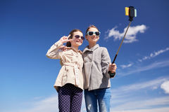 Muchachas felices con el palillo del selfie del smartphone Imagenes de archivo
