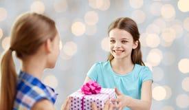 Muchachas felices con el presente de cumpleaños sobre luces Fotografía de archivo libre de regalías