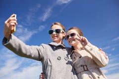 Muchachas felices con el smartphone que toma el selfie al aire libre Imágenes de archivo libres de regalías