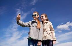 Muchachas felices con el smartphone que toma el selfie al aire libre Foto de archivo libre de regalías