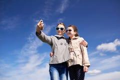 Muchachas felices con el smartphone que toma el selfie al aire libre Fotografía de archivo libre de regalías