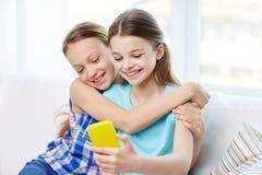 Muchachas felices con el smartphone que toma el selfie en casa Imagen de archivo